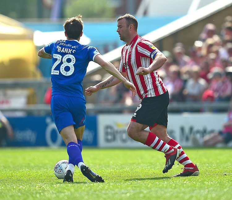 Lincoln City's Matt Rhead vies for possession with Tranmere Rovers' Oliver Banks<br /> <br /> Photographer Andrew Vaughan/CameraSport<br /> <br /> The EFL Sky Bet League Two - Lincoln City v Tranmere Rovers - Monday 22nd April 2019 - Sincil Bank - Lincoln<br /> <br /> World Copyright © 2019 CameraSport. All rights reserved. 43 Linden Ave. Countesthorpe. Leicester. England. LE8 5PG - Tel: +44 (0) 116 277 4147 - admin@camerasport.com - www.camerasport.com