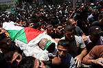 Mourners carry the body of Palestinian Mohammed Abu Halima, 22, who was shot dead by Israeli troops during clashes at Gaza-Israel border, during his funeral in Gaza city on July 7, 2018. Photo by Mahmoud Ajour