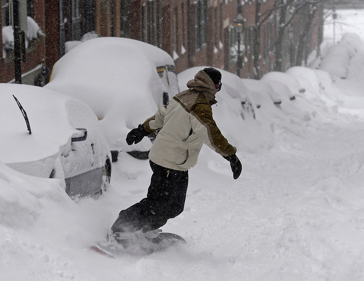 A snowboarder rides down a street in Boston's Beacon Hill neighborhood after a blizzard dumped over two feet snow in the city on Tuesday, January 27, 2015. Photo by Christopher Evans
