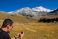 Man text messaging on cell phone in isolated Alpine meadow (Swiss Alps)