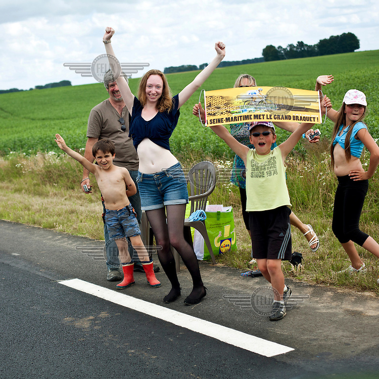 Excited spectators cheer and wave from the roadside as they await the riders of the Tour de France to pass by.