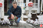 WATERTOWN, CT. 21 March 2011-032111SV05--Mark Wercnko, owner, of Mark's Gardens and Gifts cleans off snow from pansies outside his shop in Watertown Monday. Monday was the first full day of spring.<br /> Steven Valenti Republican-American