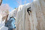 "Dan Hawes of Hanson, Massachusetts, climbs the frozen Champney Falls in the White Mountain National Forest. He uses 12 pointed crampons mounted on insulated plastic mountaineering boots, and an ice axe in each hand to aid her ascent of the waterfall. A rope attached to his climbing harness runs to an anchor at the top of the route, then down to his climbing partner and wife Jen Hawes, who ensures that he is ""on belay' in case of a slip or fall."