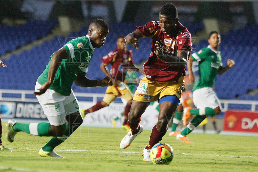 CALI - COLOMBIA -10-04-2014: Carlos Rivas (Izq.) jugador de Deportivo Cali disputan el balón con Julian Quiñonez (Der.) jugador de Deportes Tolima durante  partido Deportivo Cali y Deportes Tolima por la fecha 16 de la Liga Postobon I 2014 en el estadio Pascual Guerrero de la ciudad de Cali. / Carlos Rivas (L) player of Deportivo Cali fights for the ball with Julian Quiñonez (R) player of Deportes Tolima during a match between Deportivo Cali and Deportes Tolima for the date 16th of the Liga Postobon I 2014 at the Pascual Guerrero stadium in Cali city. Photo: VizzorImage / Juan C Quintero / Str.