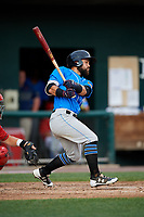 Akron RubberDucks left fielder Ka'ai Tom (4) follows through on a swing during a game against the Harrisburg Senators on August 18, 2018 at FNB Field in Harrisburg, Pennsylvania.  Akron defeated Harrisburg 5-1.  (Mike Janes/Four Seam Images)