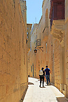 People walking narrow street historic houses in medieval city of Mdina, Malta