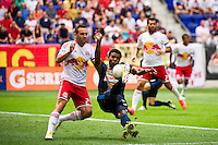 Lionard Pajoy (23) of the Philadelphia Union shoots as Brandon Barklage (25) of the New York Red Bulls defends. The New York Red Bulls defeated the Philadelphia Union 2-0 during a Major League Soccer (MLS) match at Red Bull Arena in Harrison, NJ, on July 21, 2012.