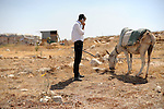 Chemi, a settler, talks on phone while out with his donkey in the unauthorized Israeli outpost of Bnei Adam, West Bank.