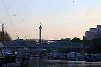 Paris Right Bank: A view of the port de l&rsquo;Arsenal in Paris (it links the Canal de Saint Martin to place de la Bastille), with its boats, its typical bridge, and the column of July on the background, in the sunrise light. There are many seagulls and the water surface is flat.<br />