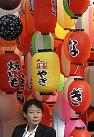 An exhibitor surrounded by paper lanterns at the 14th East China Fair in Shanghai, China. With the Yangtze Delta establishing itself as an industrial powerhouse, the East China Fair is quickly becoming an important event for information and trade of textile and light industrial products..06-MAR-04