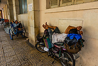 In the midday heat two men sleep atop a motorcycle and a cyclo (bicycle rickshaw), Ho Chi Minh City (Saigon), Vietnam. Vietnamese seem to be adept at sleeping almost anywhere.