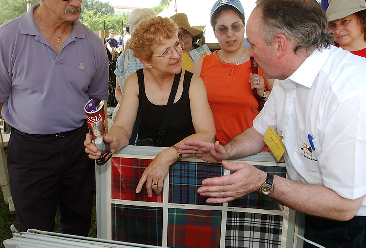 festival6/062503 - Alwyn Johnston, right, explaind Tartan cloth to Lorraine Lopardo of Mass., in the Scotland exhibit, at the 37th Annual Smitnsonian Folklife Festival.