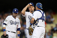 Joe Blanton #56 of the Los Angeles Dodgers is visited on the mound by Adam Kennedy #3 and A.J. Ellis #17 during a game against the San Francisco Giants at Dodger Stadium on August 21, 2012 in Los Angeles, California. San Francisco defeated Los Angeles 4-1. (Larry Goren/Four Seam Images)