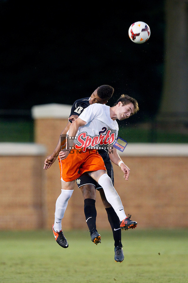 Ryan Zinkhan (21) of the Virginia Cavaliers heads the ball away from Rafael Fagundo (3) of the Wake Forest Demon Deacons at Spry Soccer Stadium on September 13, 2013 in Winston-Salem, North Carolina.  The Demon Deacons defeated the Cavaliers 3-2.  (Brian Westerholt/Sports On Film)