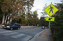 A tilted view of a pedestrian road sign and a crosswalk with cars passing by in early evening. Cupertino, California, USA