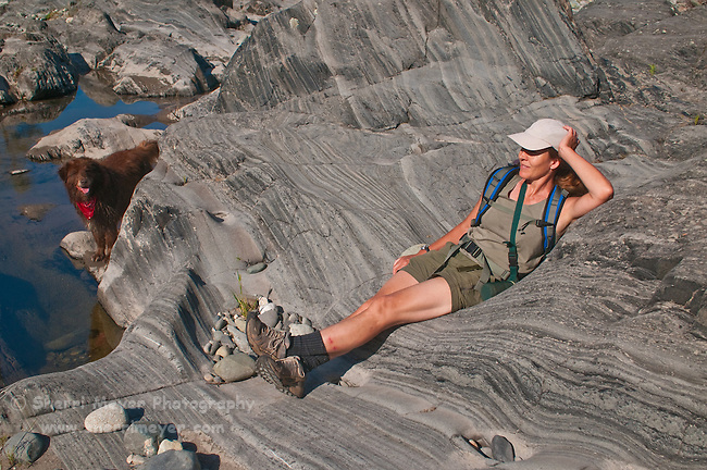Woman relaxing on a rock, while her dog watches, North Fork of the American River, Weimar, California.