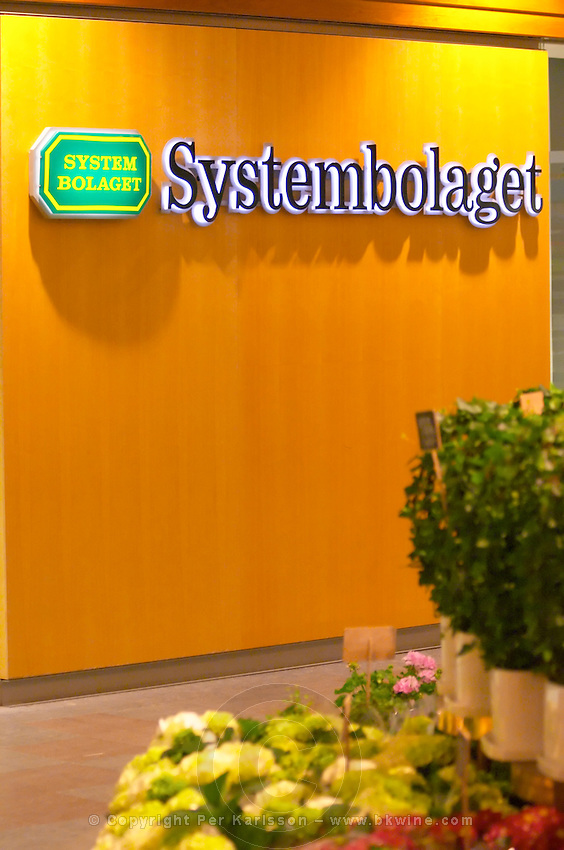 A neon sign saying Systembolaget, the Swedish retail monopoly stores for alcohol wine beer spirits and flowers in a flower shop in the foreground. Stockholm, Sweden, Sverige, Europe