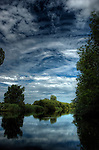 Blue sky and white clouds reflected in a peaceful river