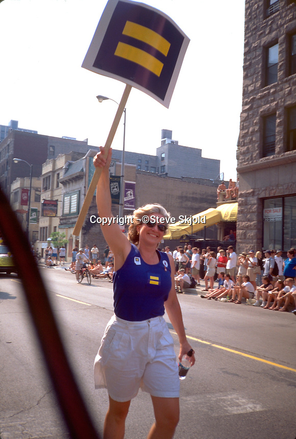 Woman 37 holding gay and lesbian equality sign at the pride parade.  Chicago Illinois USA