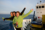 Three girls enjoy the setting sun on the bow of a ship in the Arctic.