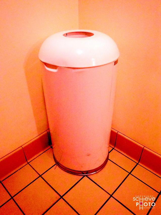 Color enhanced trash can in a restaurant bathroom.
