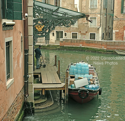 Venice, Italy - March 24, 2006 --  Bottles of water are delivered to a hotel in Venice, Italy on March 24, 2006.  Since there are no paved roads in Venice, all merchandise and supplies come into the city by boat.  Note the steps under the wooden dock in the photo.  These steps once were used to reach the boats.  Today, they cannot be used because they are submerged most of the time because Venice is slowly sinking into its lagoon..Credit: Ron Sachs / CNP
