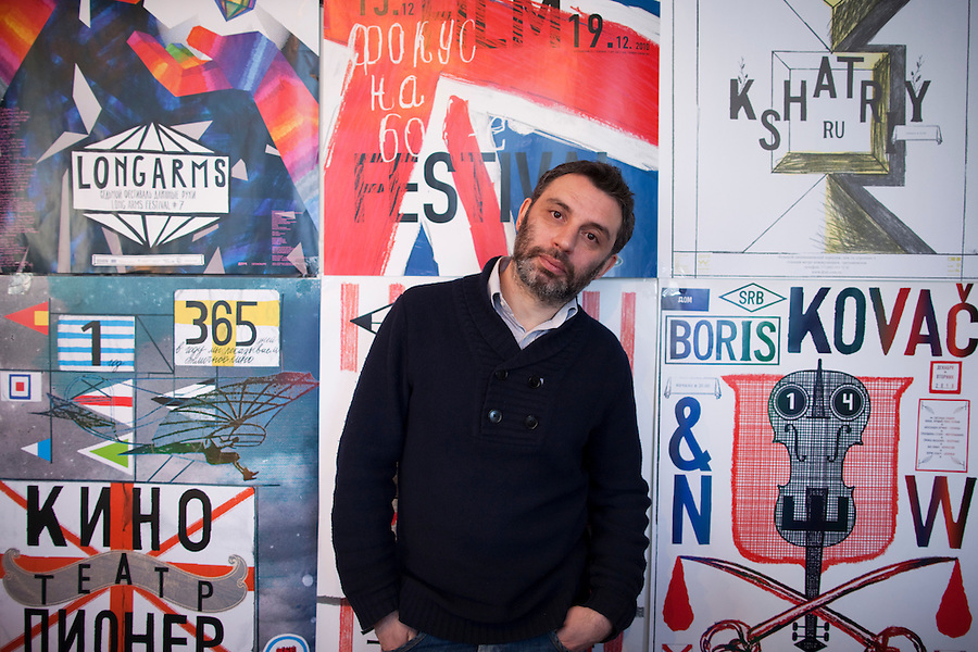 Moscow, Russia, 16/02/2011..Designer Igor Gurichov at his studio with posters from his design company.