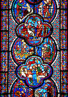 Medieval stained glass Window of the Gothic Cathedral of Chartres, France - dedicated to St John The Evangelist. Bottom left - Armourers making shields and saddles, above right - Armourers making stirrups. Central bottom panel - Death of Satheus, above left - John's journey into exile on Patmos, above right - St John on Patmos. Central top panel - St John confronting Aristodemus, above left and right - The raising of Drusiana . A UNESCO World Heritage Site..