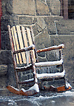 An old rocking chair, with icycles hanging from it, sits on a porch in front of a stone wall.