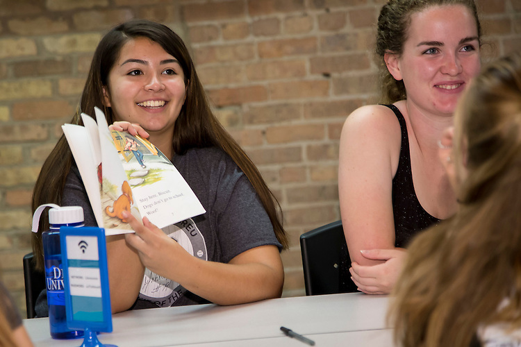Stevie Rodriguez, freshman, College of Science and Health, offers comments while volunteering for the Sit, Stay, Read organization Tuesday, Sept. 8, 2015, as part of her class's New Student Service Day volunteer work. The group of students aimed to write several hundred personal notes to grammar school students who will participate in the Sit, Stay, Read program during the 2015 school year. Sit, Stay, Read's mission is to improve literacy skills and foster a love of learning in at-risk children. Founded in 2003, the organization brings teams of trained volunteers and certified reading assistance dogs to Chicago Public Schools and inner-city community programs. Nearly 1200 incoming students participating in the Discover Chicago program wrapped up their week of immersion by volunteering with area non-profits and community groups as part of DePaul University's New Student Service Day. (DePaul University/Jeff Carrion)