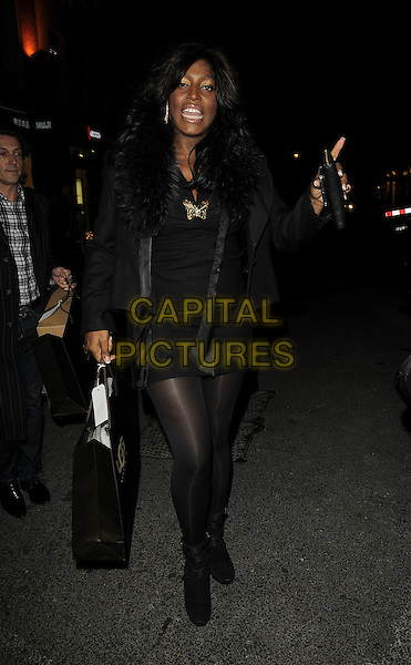 MICA PARIS .The UGG Australia: London Store Launch in Covent Garden, London, England. .November 26th, 2008 .full length black skirt jacket fur collar trim tights boots bag purse funny face hand.CAP/CAN.©Can Nguyen/Capital Pictures.