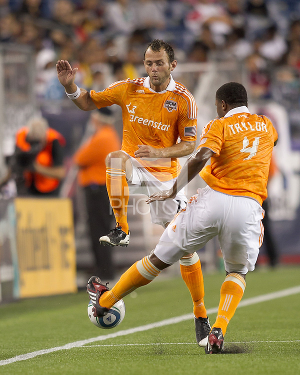 Houston Dynamo defender Jermaine Taylor (4) attempts to dribble and avoid oncoming teammate, Houston Dynamo midfielder Brad Davis (11). In a Major League Soccer (MLS) match, the New England Revolution tied Houston Dynamo, 1-1, at Gillette Stadium on August 17, 2011.