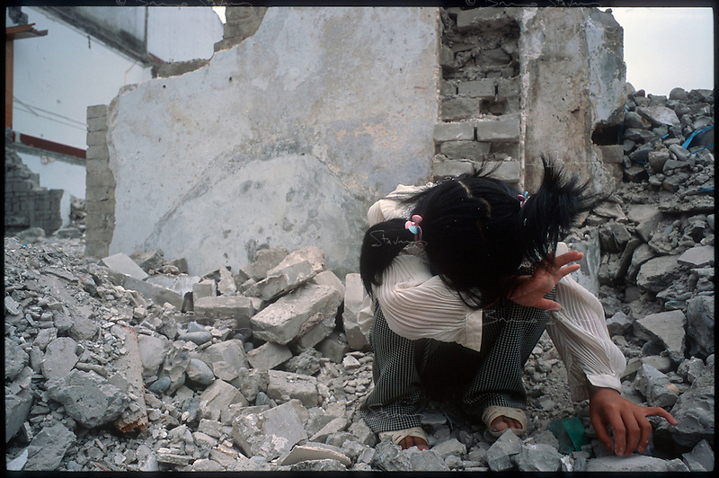 Fengdu, China, August 2003.A little girl playing in the ruble of the .old city of Fengdu, already half-destroyed to allow the Three Gorges Dam project to be completed.