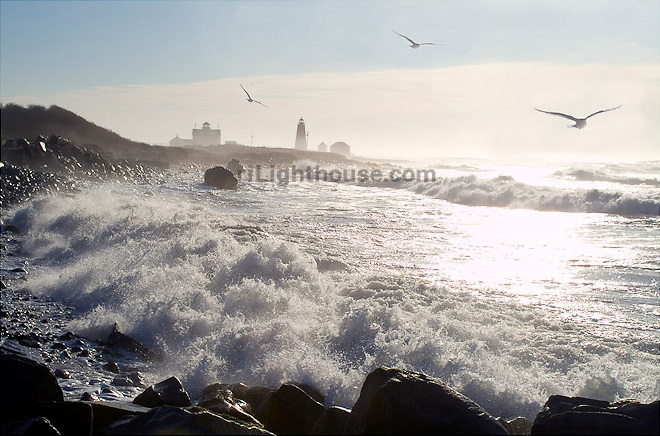 Seagulls fly above the surf at Watch Hill Lighthouse
