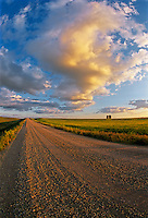 Gravel road and clouds at sunset. Cypress River, Manitoba