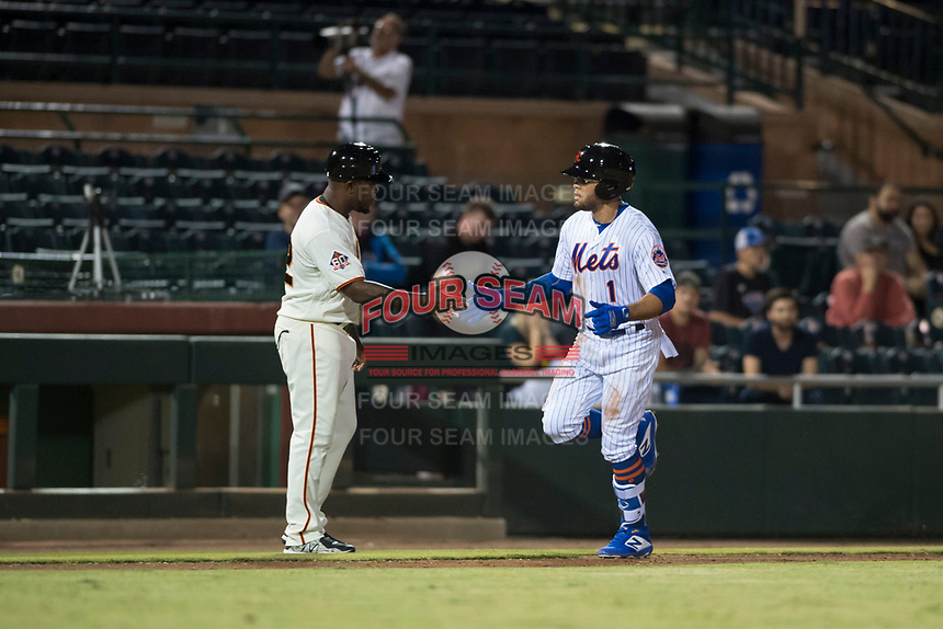 Scottsdale Scorpions center fielder Desmond Lindsay (1), of the New York Mets organization, is congratulated by manager Willie Harris (22) after hitting a home run during an Arizona Fall League game against the Salt River Rafters at Scottsdale Stadium on October 12, 2018 in Scottsdale, Arizona. Scottsdale defeated Salt River 6-2. (Zachary Lucy/Four Seam Images)