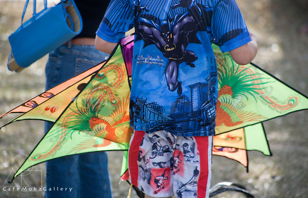 Flying kites, Easter, boy with batman shirt and patterned shorts and kites