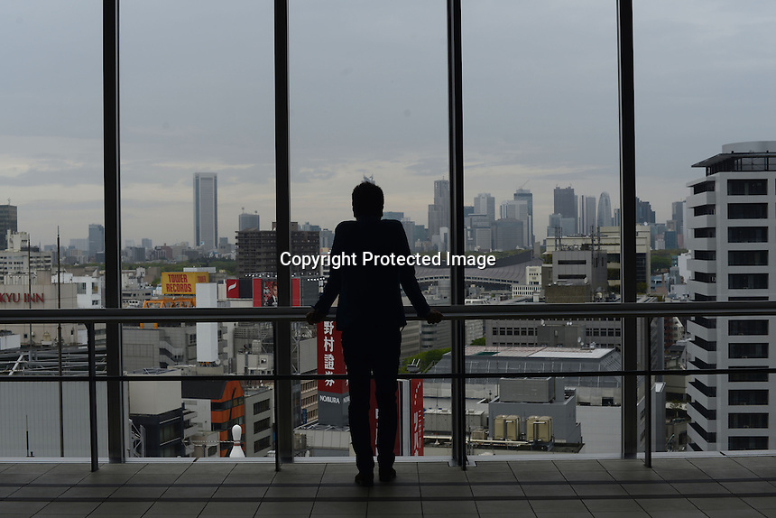 A BUSINESSMAN IS LOOKING AT SHIBUYA FROM BIG WINDOW SHIBUYA