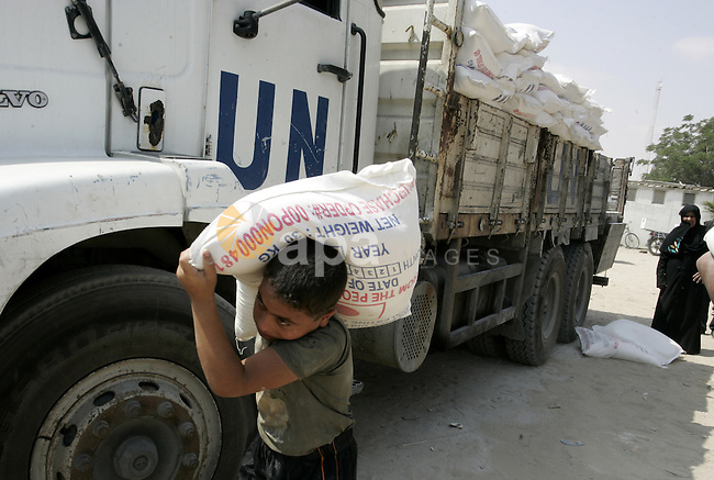 Palestinians receive humanitarian aid at the United Nations aid distribution centre in the refugee camp of Rafah in the southern Gaza Strip on July 7, 2011. United Nations Relief and Works Agency (UNRWA) decide to change its name and reduce its services in the Palestinian territories. Photo by Abed Rahim Khatib