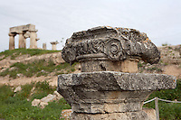 CORINTH, GREECE - APRIL 16 : A detail of an Ionic capital, on April 16, 2007 in Corinth, Greece. This Ionic capital amongst the ruins of Corinth is seen in the early morning light with the Temple of Apollo in the background. Standing prominently on a knoll the Temple of Apollo is one of the oldest temples in Greece. It was built in the 7th century BC in the Doric Order and seven of its original 38 columns remain. Corinth, founded in Neolithic times, was a major Ancient Greek city, until it was razed by the Romans in 146 BC. Rebuilt a century later it was destroyed by an earthquake in Byzantine times. (Photo by Manuel Cohen)