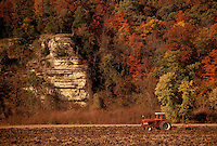 Red tractor in field under bluff