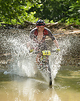 NWA Democrat-Gazette/BEN GOFF @NWABENGOFF<br /> Duncan Warner, a category 1 racer from Bentonville, fords a creek Sunday, July 16, 2017, during cross country races on the final day of the 19th annual Fat Tire Festival at Lake Leatherwood City Park in Eureka Springs.