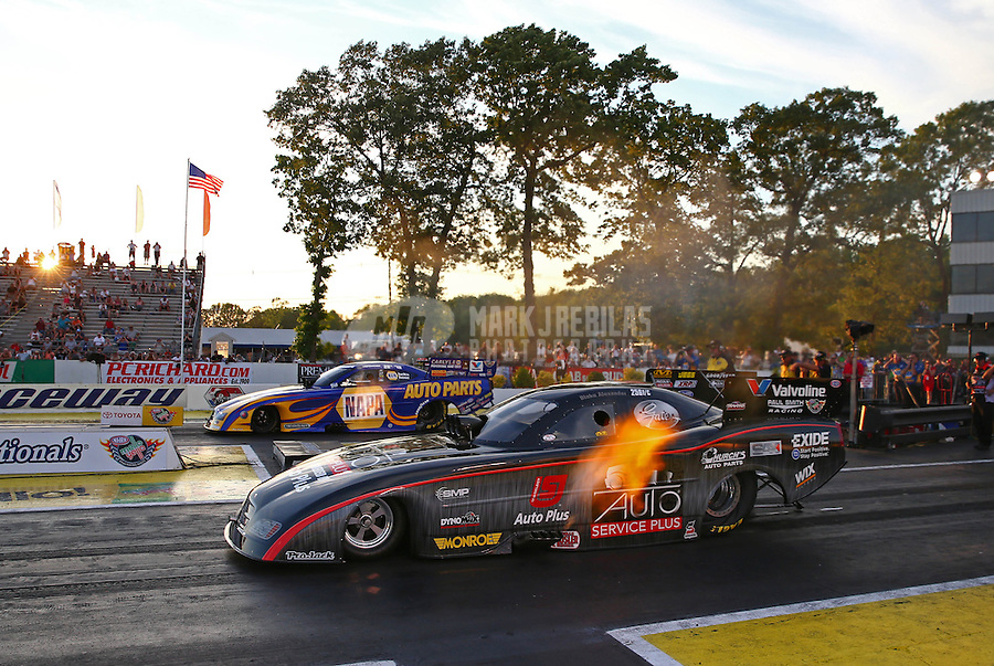 May 31, 2013; Englishtown, NJ, USA: NHRA funny car driver Blake Alexander (near lane) races alongside Ron Capps during qualifying for the Summer Nationals at Raceway Park. Mandatory Credit: Mark J. Rebilas-