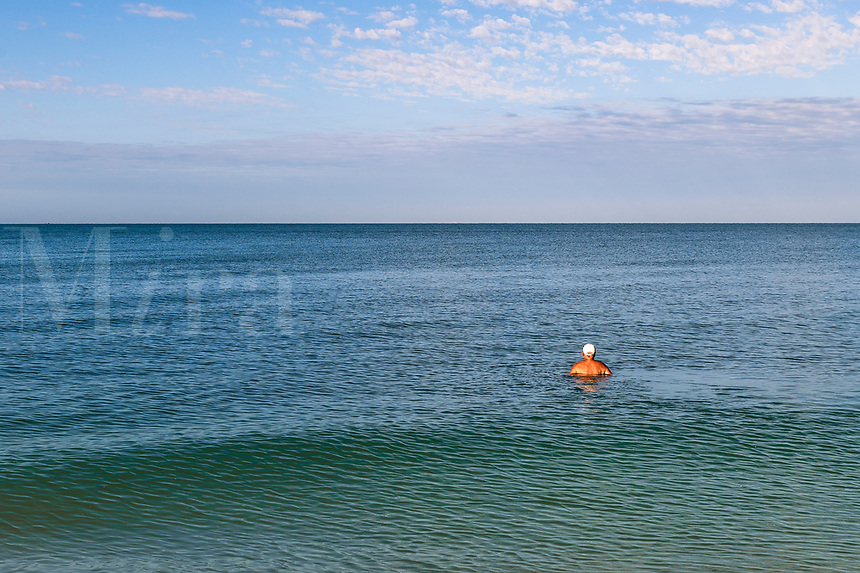 Senior man swimming in the ocean and viewing horizon, Barefoot Beach