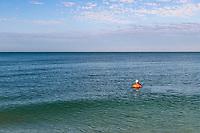 Senior man swimming in the ocean and viewing horizon, Barefoot Beach