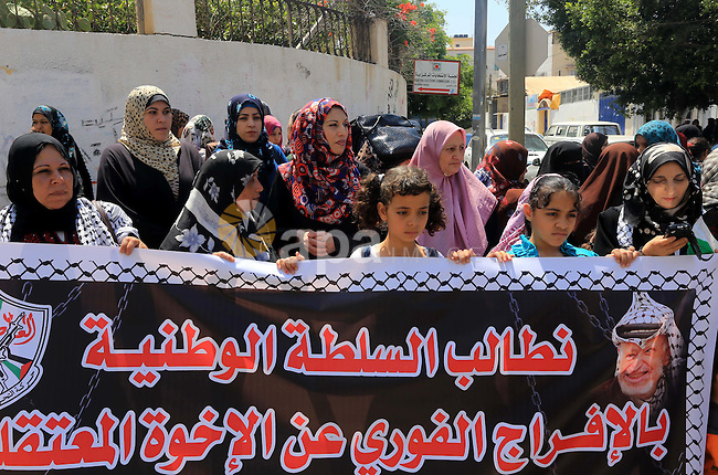 Palestinians who support PLC member of Fatah Mohammed Dahlan, hold banners during a protest demanding Palestinian Authority to release their relatives detained in its jails in Gaza on June 16, 2015. Photo by Mohammed Asad