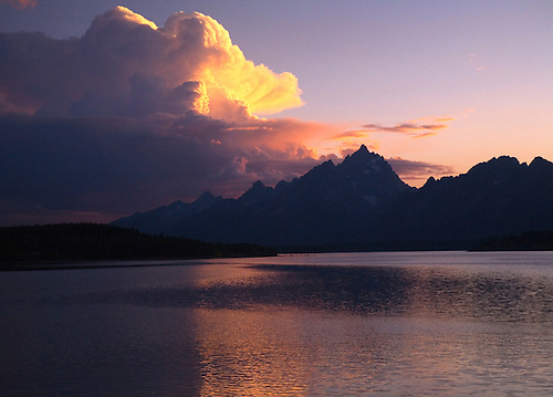 THE SUN SETS BEHIND THE TETON MOUNTAIN RANGE BEHIND JACKSON LAKE AT THE GRAND TETONS NATIONAL PARK,WYOMING