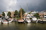Sailing boats in Maartensgat harbour with dramatic lighting after recent rain storm, Dordrecht, Netherlands