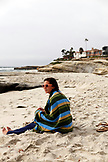USA, California, San Diego, Casey sits wrapped in a towel at Wind And Sea Beach