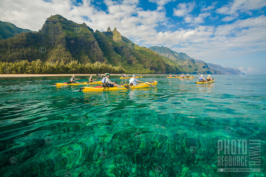 Sea kayakers on a group tour paddle in the clear waters along Kaua'i's Na Pali coastline.